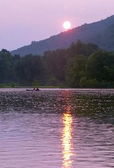 Two kayakers enjoy a summer sunset on the Chemung River.