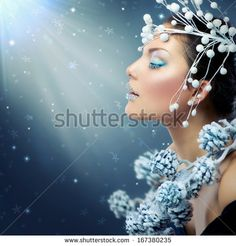 Winter Beauty Woman. Christmas Model Girl Makeup. Holiday Make-up. Snow Queen High Fashion Portrait over Blue Snow Background. Eyeshadows, False Eyelashes and Crystals on the Lips.   - stock photo