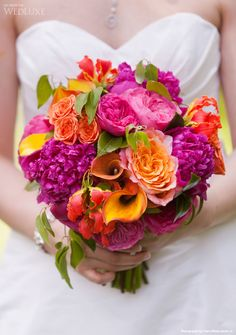 Amazing bright coloured bouquet with fuschia peonies, pink garden roses, orange spray roses, gloriosa, mango callas and free spirit roses.