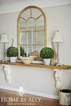 Cette étagère est simplement constituée d'une planche de bois verni.Deux lampes et deux pots de fleurs font office de décoration.Le miroir permet d'illuminer la pièce et ajoute du cachet à la pièce.