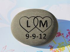 "Custom engraved stone with  interlocked hearts with your personalized Initials and date. Our stones are deeply engraved  in a natural gray stone.  Stone colors vary. The stones are approx. 3-5"" across."