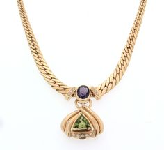 Crewneck, in 18ct(750/1000) yellow gold, 30,35gr, 80's years. Crewneck in graduated boxed gourmette mesh with a central pendant, fits 11 brilliant-cut diamonds of about 0,22ct H/VS, a 9x12mm natural russian amethyst of about 2,5ct and a 11x11mm peridot of triangular cut