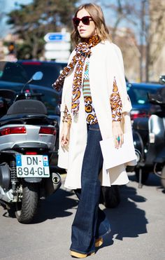 Kseniya Sobchak wearing a cape, printed top, and flared jeans