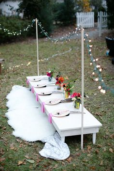 """""""We set out several toddler-sized tables (we somehow have quite a few play tables on hand),"""" Joni says. """"We added in a couple of low benches, and my dad custom built a really adorable eight-foot-long banquet table! The tables were set with bamboo plates and forks, pink and white straws, a wooden necklace, and a feather headdress.""""  Source: Lay Baby Lay"""