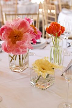 Place a few simple arrangements with only a few flowers per vase together for a more dynamic center display