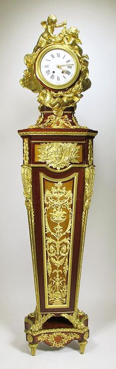 """A Very Fine French 19th Century Louis XVI style ormolu-mounted amaranth, tulipwood, sycamore and parquetry pedestal """"Régulateur de Parquet"""" Clock, Attributed to Alfred Emmanuel Louis Beurdeley (French, 1847-1919) After the model attributed to Jean-Henri Riesener, surmounted by a cloud-form case cast with three putti suspending garlands, centred by a white enamel dial with Roman numerals, on a spreading socle with ribbon-hung garlands, above the square tapering pedestal headed by a laurel…"""