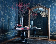 In this Manhattan foyer a hand-painted wall covering by de Gournay adorns the wall, the antique French mirror is from Bijan Royal, and the rug is by Stark.