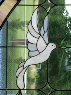 A white dove stained glass window. The presence of the feminine, symbolized as the Holy Spirit in the Trinity.