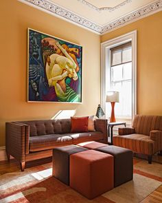 living room for art collectors by www.down2earthdesign.com. Photo by Paul Loftland  gold walls, orange and brown upholstered cubes.