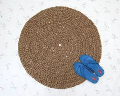 """Here's a handmade round jute rug, measuring about 33"""" across. It's crocheted with a double thickness of all natural jute twine, and is roughly 1/2"""" thick. The thickness makes it nice on your feet, so it would be a nice choice for the foot of an armchair. Or it would look great in a foyer or as a kitchen rug. The rustic look of the natural jute will suit almost any decor, and complement any room.  Not the right size? No problem, I can make this up for you in any size, up to 48"""" in diameter…"""