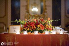 Wedding sweetheart table with orange, red, and  yellow centerpiece -- but i would do a dark purple for the table cloth