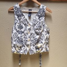 GAP Vest w Floral Print Used - navy blue with cream or pearl white color - 3 pockets on the front (miniature and almost invisible) - slim fit at the waist and rises a bit once bow is tied in back - okay condition GAP Tops