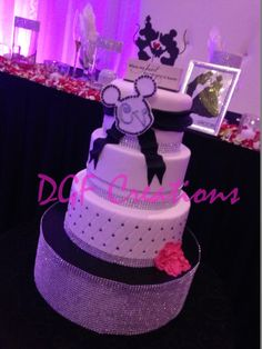 Mickey and Minnie mouse wedding theme cake with little fuchsia carnation flower on the side of the cake.