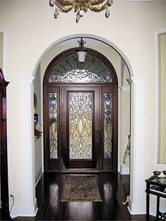 """Door Style DbyD-1031. This gorgeous Front Exterior Entry shows a Mahogany 36"""" x 80"""" Style """"F"""" Door with Fluted Molding, Rosettes, Ledge and Dentil. The Sidelites are Mahogany 12"""" x 80"""" Style """"F"""" Sidelites. The Front Exterior Entry is completed with a Mahogany Radius Transom. The Leaded Beveled Glass was built by Doors by Decora. The Hardware is Baldwin Springfield 6573-003. The stain color is Traditional Mahogany."""