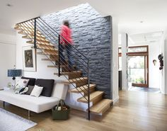 open wood stairs.  contemporary railing.  textured rock wall.  big windows.  open plan.   i am IN LOVE.