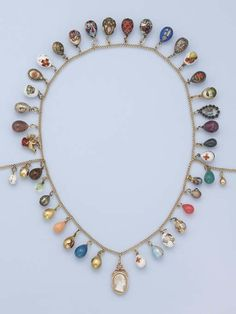 A RUSSIAN EGG NECKLACE The curb-link gold necklace suspending thirty-eight enamel, gem-set and hardstone egg pendants and three other pendants, 50.0 cm. long, most eggs with Russian marks