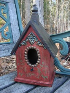 The vintage charm of this Village Bird House comes from the unusual play of color and the metal accents