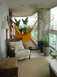 the horizontal slat panel for plantings, the hammock and the use of large plants make this balcony quite comfortable and inviting!