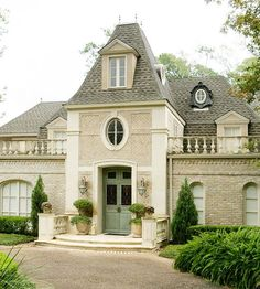 Once a vaguely Italianate ranch, this home underwent dramatic renovations to become the gracious French manor it is today. Texas limestone surrounds the entrance, while soft green antique double doors welcome guests. The home boasts a bevy of country French features, such as a dovecote tower, old French balusters, zinc oeil-de-boeuf dormers, and a mansard-style roof.