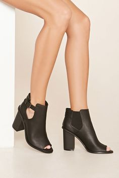 This pair of booties features side cutouts with a buckle closure, a stacked heel, a peep-toe, and elasticized side paneling.