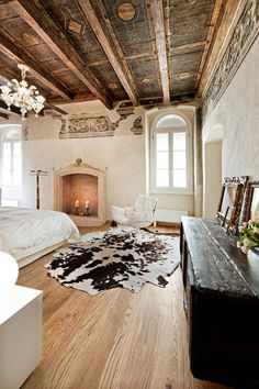 Exposed wood beam ceiling, cowhide rug, neutral and natural bedroom with white walls.