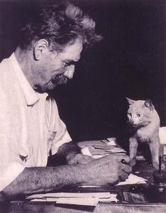 Albert Schweitzer à son bureau avec son chat; [Mi-corps, profil à dr.]; [A. Schweitzer (1875-1965) pasteur, théologien, philosophe, médecin, musicologue et organiste français, membre de l'Académie des sciences morales et politiques (1951), prix Nobel de la paix (1953)]