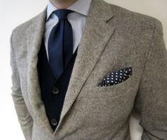 Grey blazer, navy cardigan, navy tie, white shirt, polka dot pocket square.