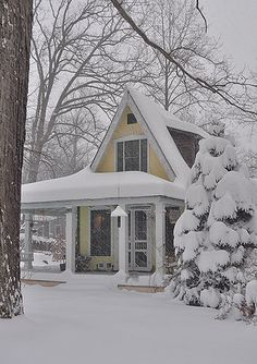 Pretty yellow cottage blanketed in snow