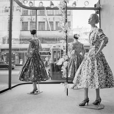 A large storefront window (in Stockholm) during the 1950s filled with three mannequins sporting wonderfully pretty frocks.