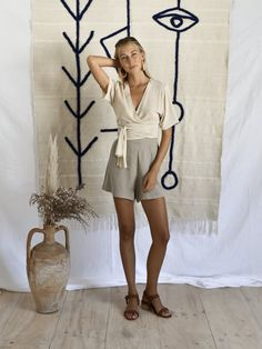 ISIBÉAL WRAP | SAND Short sleeve wrap top in cashmere cotton blend in Sand Also available in Dried herb cashmere cotton blend Available in O/S, 'one size', wrap style, adaptable to suit Cool machine wash. line dry. do not bleach. please use environmentally friendly detergents