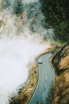 Car driving in foggy mountain highway, Hokkaido, Japan.   By Yiu Yu Hoi.