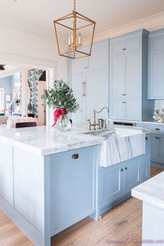 Inside Our Vintage Modern Style Holiday Kitchen... Sharing a peek inside our powder blue and white marble kitchen all decked out for Christmas!   kitchen-gray-cabinet-color-white-marble-countertops-calcutta-gold-black-barstools-vent-hood-gold-trim-modern-vintage-open-shelving-antique-brass-cup-pull-knob-whitewashed-hardwood-flooring-long-white-subway-tile-backsplash-scalloped-marble-piece-behind-stove