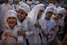 Indian Sikh schoolgirls laugh during a Sikh religious procession in New Delhi, India.