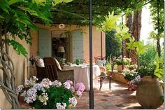 love the ivy covered arbor and painted shutter doors; inviting space