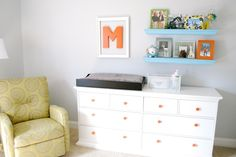 I love the orange knobs on the dresser, as well as the decor style above