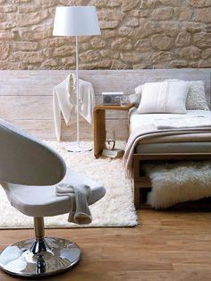 Un dormitorio en blanco con pared de piedra vista