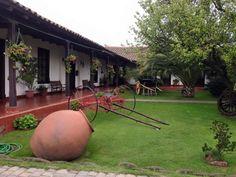 Vista cuidado patio exterior con objetos de época y vegetación bien cuidada