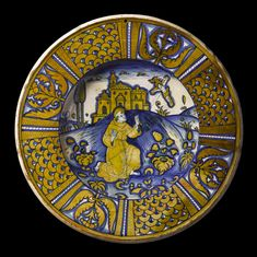 Maiolica dish painted in yellow and blue lustre with St Francis of Assisi receiving the stigmata and with scale pattern and floral ornament on the rim: Italian, Deruta, c. 1550 - 1570