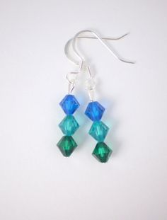 These gorgeous blue and green bead earrings are made with high-quality capri blue, blue zircon, and emerald green Swarovski crystal beads. These beaded earrings are similar to the beautiful colors of the ocean; refreshing, soothing, and invigorating. These earrings come in a cute organza bag ready for gifting.  LENGTH: 1 & 1/2 inches total (ear wire to end of lowest bead)