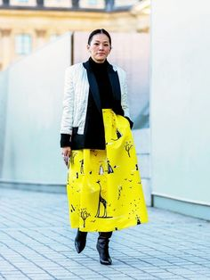 A black turtleneck is paired with a black and white jacket, printed maxi skirt, and leather boots