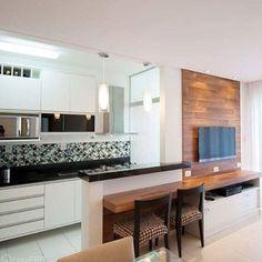 Cozinha americana e sala de estar integradas | Amamos o painel para TV em madeira com prateleira até o balcão da cozinha. Uma opção para quem deseja uma mesa para refeições rápidas. Invista! #ambientesintegradosmeunovoapê Foto: Reprodução/Pinterest
