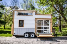A beautiful tiny home available for sale in Zionsville, Inadiana. There's a drop-down deck, rooftop patio, and a glass garage door!