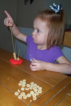 Stacking cereals loops on spaghetti stuck in playdough. Fruit Loops have larger center holes than Cheerios. (Choose according to child's age.)