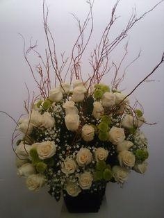 Arreglo de rosas color perla decorado con ramas secas
