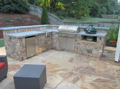 Stacked stone outdoor kitchen with Pennsylvania bluestone countertops in Cobb County GA Includes FireMagic grilling equipment and accessories and a green egg.