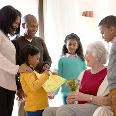 Eine Familie kümmert sich ganz lieb um eine ältere Dame, die aus einem anderen Land kommt