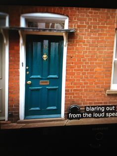 Glossy teal front door with red brick. Make the front entrance pop.