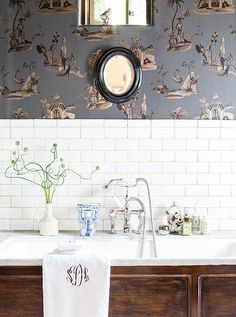 Inside the Home of Lulu Powers -- This stunning white and bright tiled bathroom gets a jolt of antique vintage French country style from an old-school sink faucet and gorgeous landscape mural wallpaper in a stunning blue gray with metallic accents.  Take the full tour of the designers stunning classic and colorful home on our Style Guide!