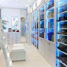 White cabinetry with glass fronts in a large walk-in closet
