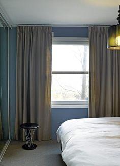 Gardinene dekker veggene på hver side av vinduet. Slik kan man forledes til å tro at vinduet egentlig er større enn det er. Gyngekrakken er fra Vitra.